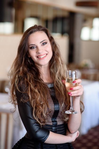 Ein schönes mädchen trinkt champagner in einem restaurant. Premium Fotos