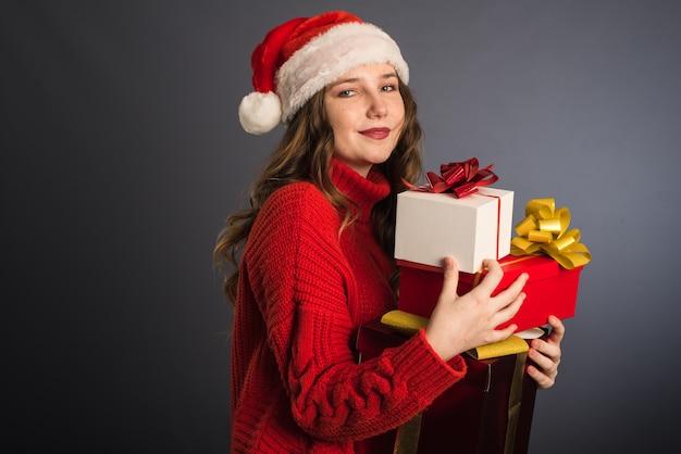 Ein schönes modell mit einer weihnachtsmannmütze und einem roten strickpullover hält viele geschenke in ihren händen. Premium Fotos