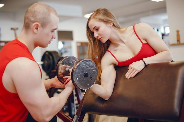 Ein schönes und athletisches sportkleidungsmädchen, das in der turnhalle mit freund ausbildet Kostenlose Fotos