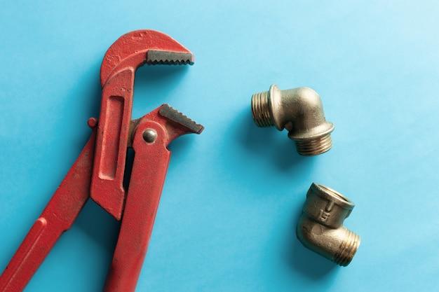 Ein schraubenschlüssel auf dem blauen hintergrund mit einigen passenden verbindungsstücken. für design und dekoration Premium Fotos