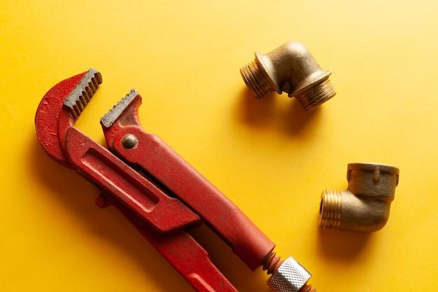 Ein schraubenschlüssel auf dem gelben hintergrund mit einigen passenden verbindungsstücken. für design und dekoration Premium Fotos