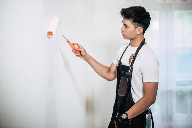Ein schreiner hält einen pinsel und malt holz. Kostenlose Fotos