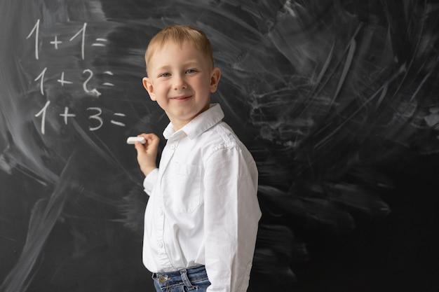 Ein schüler steht an der tafel im klassenzimmer und schreibt beispiele in mathematik. der junge lächelt. positiver schüler im unterricht. zurück zur schule. mathematikunterricht in der grundschule. Premium Fotos