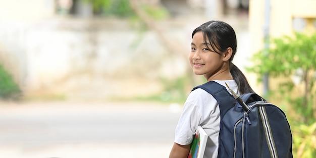 Ein schulmädchen hält eine malausrüstung in der hand und trägt eine schultasche, während es auf einen schulbus wartet. Premium Fotos