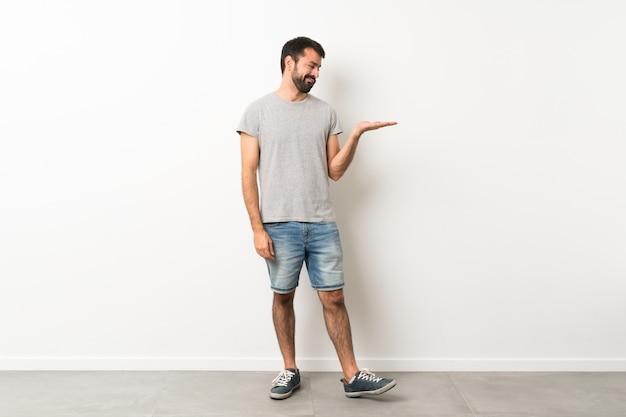 Ein schuss in voller länge des gutaussehenden mannes mit dem bart, der copyspace mit zweifeln hält Premium Fotos