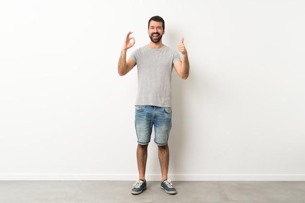 Ein schuss in voller länge des gutaussehenden mannes mit dem bart, der okayzeichen und daumen herauf geste zeigt Premium Fotos