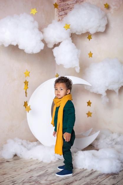 Ein schwarzer kleiner junge in einem grünen pullover und einem gelben schal kostet nachdenklich etwa einen monat. ein kleiner prinz. kleiner afroamerikaner. nachdenkliches kind. das kind hat spaß und spielt im kindergarten. schule Premium Fotos
