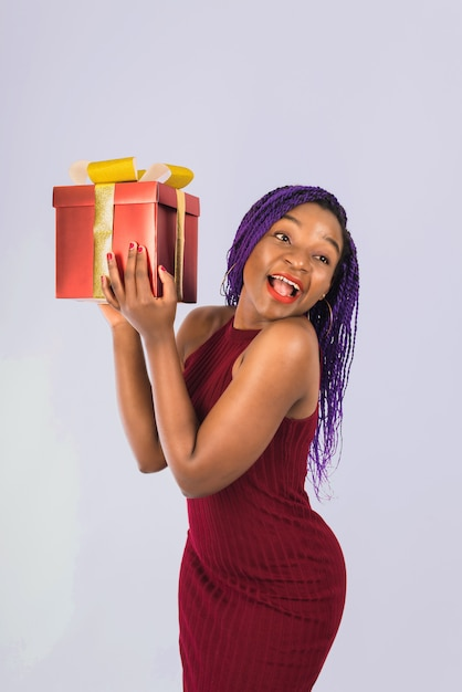 Ein schwarzes mädchen genießt ein weihnachtsrotes großes geschenk. mädchen lächelt und erhält geschenk. Premium Fotos