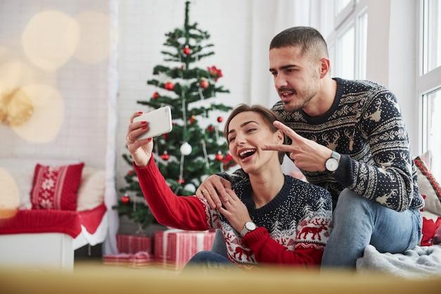 Ein selfie machen. kerl, der geste von zwei fingern zeigt. glückliche junge leute sitzen auf der fensterbank im raum mit weihnachtsdekorationen Premium Fotos