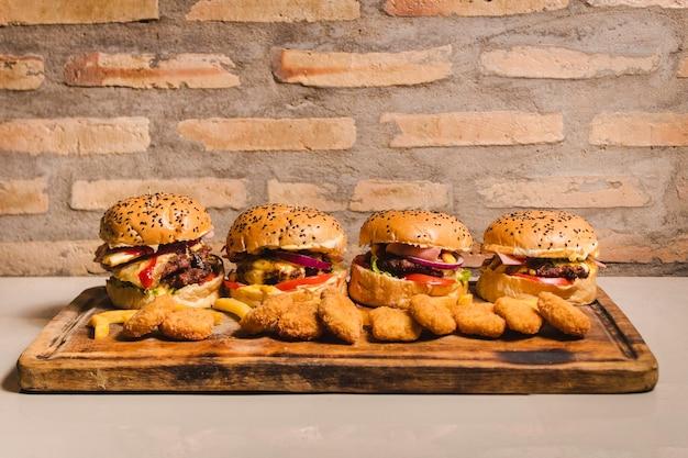 Ein set mit vier köstlichen hamburgern unterschiedlicher größe, die rundum mit nuggets gefüllt sind Premium Fotos