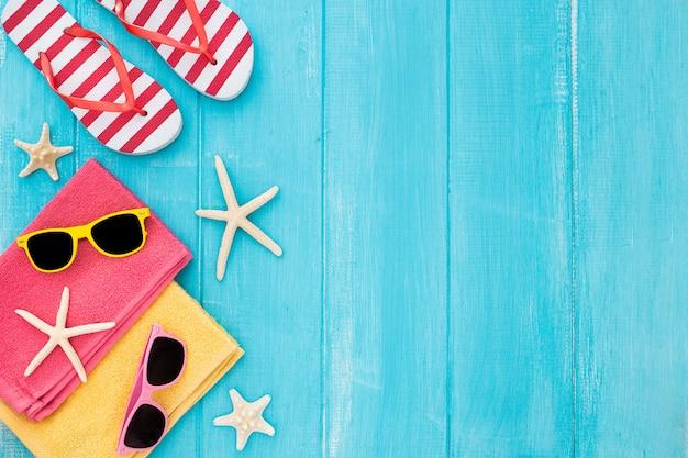 Ein sonnenbad nehmender strandhintergrund des sommers, sonnenbrille, flipflops, kopienraum auf blauem hölzernem hintergrund Kostenlose Fotos