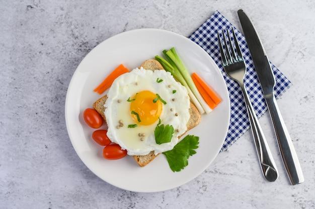 Ein spiegelei, das auf einem toast liegt und mit pfeffersamen mit karotten und frühlingszwiebeln belegt ist. Kostenlose Fotos
