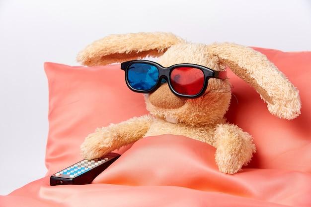 Ein spielzeugkaninchen in einer stereobrille mit einer fernbedienung vom fernseher liegt im bett. Premium Fotos