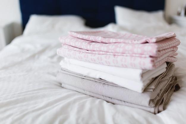 Ein stapel sauberer und gebügelter wäsche liegt auf dem bett Premium Fotos