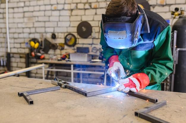 Ein starker mann ist schweißer in einer schweißmaske und schweißt leder, ein metallprodukt wird mit einem schweißgerät in der garage geschweißt Premium Fotos