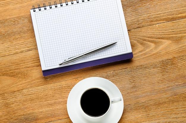 Ein stift auf einem notizblock und eine kaffeetasse auf einem holztisch. Premium Fotos