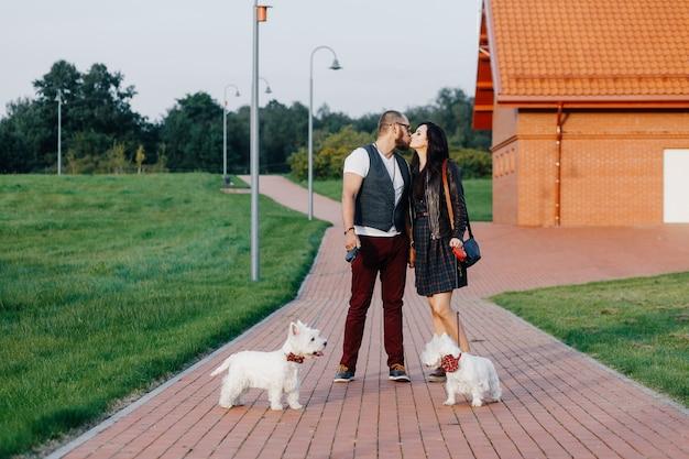 Ein stilvolles paar schlendert mit zwei weißen hunden durch den park Premium Fotos