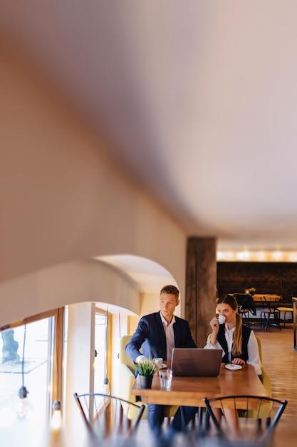Ein stilvolles paar trinkt morgens kaffee im café und arbeitet mit einem laptop, jungen geschäftsleuten und freiberuflern Premium Fotos