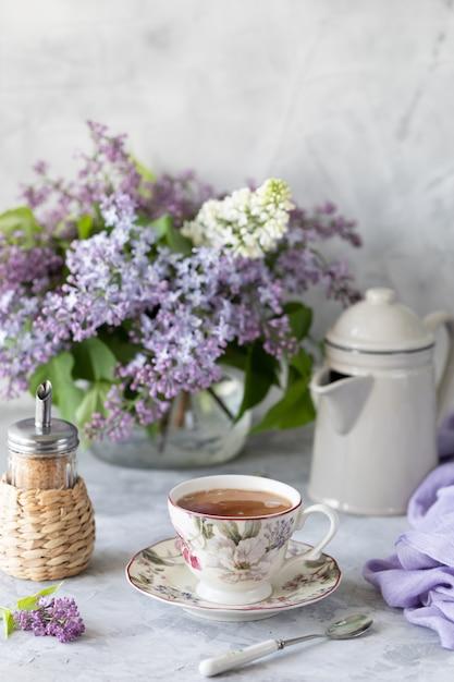 Ein strauß flieder, eine tasse kaffee Premium Fotos