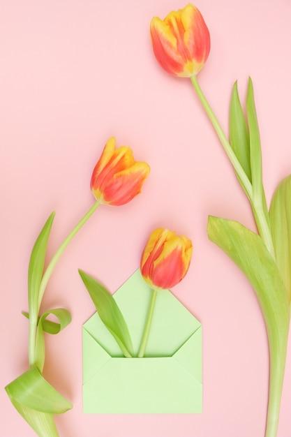 Ein strauß tulpen und ein umschlag mit einer notiz auf einem tendernes rosa hintergrund. konzept des internationalen frauentags, muttertag, ostern Premium Fotos