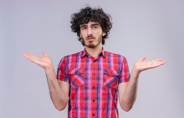 Ein stressiger gutaussehender mann mit lockigem haar in kariertem hemd, mit offenen armen Kostenlose Fotos
