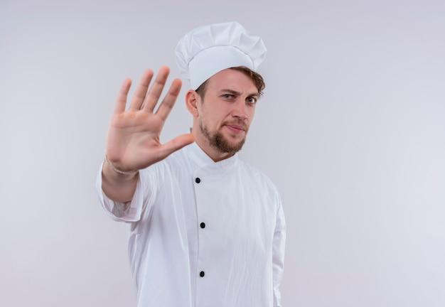 Ein stressiger junger bärtiger kochmann, der weiße kochuniform und hut trägt, die stoppgeste mit hand zeigen, während auf einer weißen wand schauen Kostenlose Fotos
