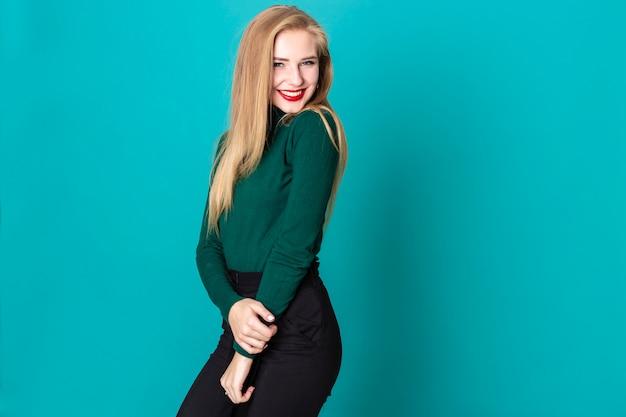 Ein studio schoss von der verlockenden blonden frau, die playfully die kamera betrachtet Premium Fotos