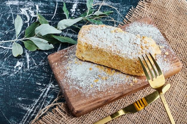 Ein stück honigkuchen auf einem holzbrett. Kostenlose Fotos