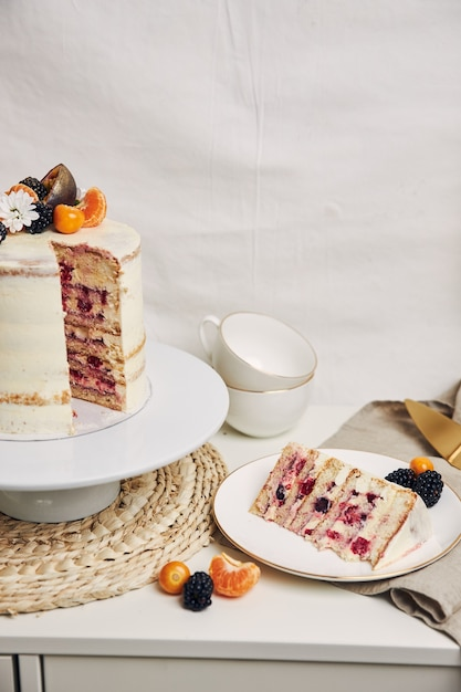 Ein stück kuchen mit beeren und passionsfrüchten auf dem tisch hinter einem weißen hintergrund Kostenlose Fotos