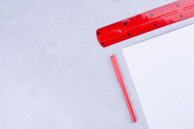 Ein stück papier mit rotem lineal und kohlestift. Kostenlose Fotos