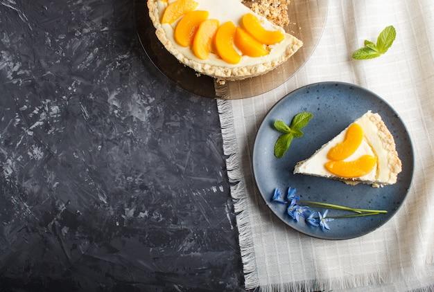 Ein stück pfirsichkäsekuchen auf einer blauen platte mit blauen blumen auf einem schwarzen hintergrund. Premium Fotos