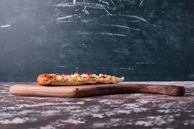 Ein stück pizza auf blau. Kostenlose Fotos