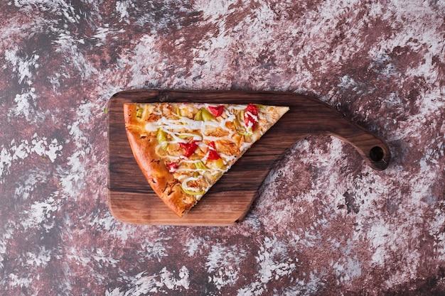 Ein stück pizza auf einem holzbrett, draufsicht Kostenlose Fotos