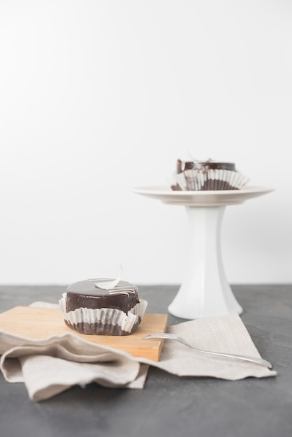 Ein stück schokoladenkuchen mit verpackung auf schneidebrett und kuchen stehen auf grauem schreibtisch Kostenlose Fotos