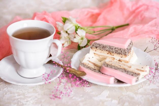 Ein süßer rosa rosentassenkuchen mit teekanne und tasse auf dem tisch Premium Fotos
