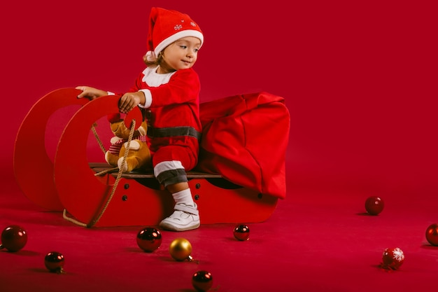 Ein süßes kleines mädchen in einem roten weihnachtsmannkostüm, auf einem schlitten, begleitet von rentieren mit geschenken und winterdekorationen. Premium Fotos