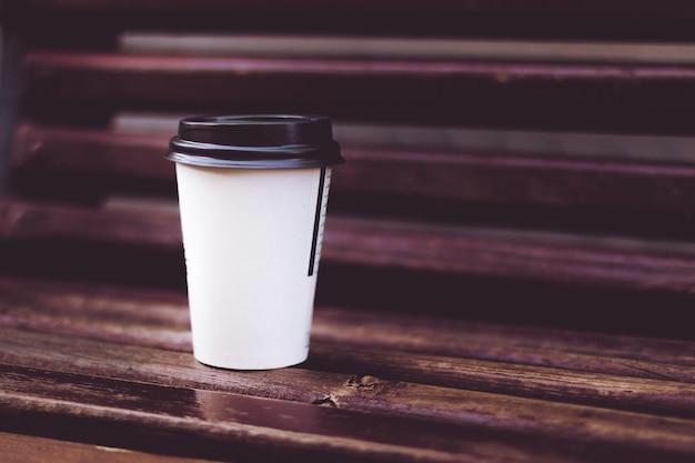 Ein tasse kaffee auf der holzbank im park Premium Fotos
