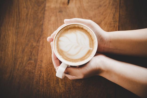 Ein tasse kaffee in der hand von frauen auf hölzerner beschaffenheit. Kostenlose Fotos