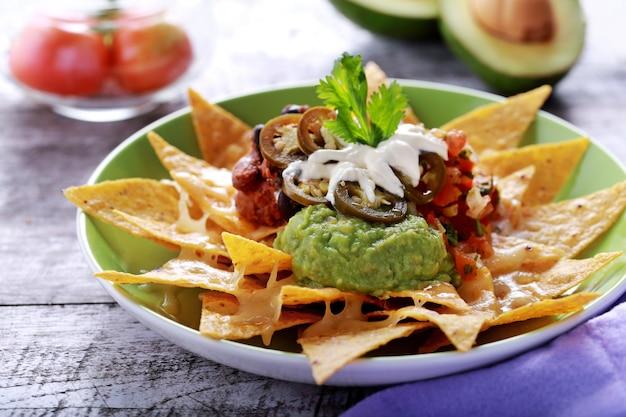 Ein teller mit hausgemachten corn chips mit vegetarischem bohnen-chili, mozarella und jalapenos Premium Fotos