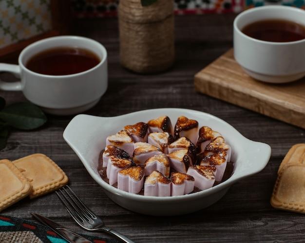 Ein teller mit herzförmigen vanille-keksen, kekse mit tassen tee Kostenlose Fotos