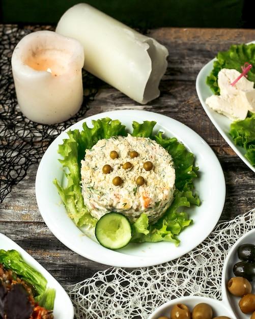 Ein teller mit oliviesalat, garniert mit gurke und salat Kostenlose Fotos