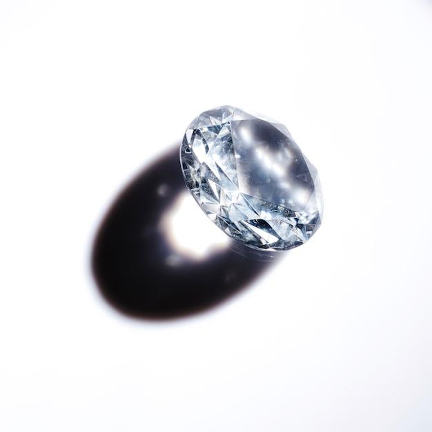 Ein teurer kristalldiamant mit schatten auf weißem hintergrund Kostenlose Fotos