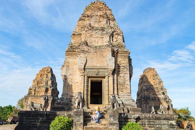 Ein tourist, der angkor-ruinen unter dschungel, angkor wat tempelkomplex, reiseziel kambodscha besucht. frau mit traditionellem hut, hintere ansicht. Premium Fotos
