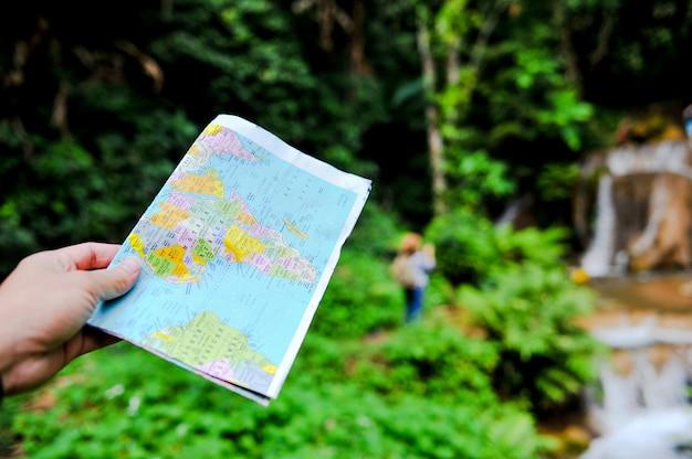 Ein tourist und seine karte auf einer reise zum wald in thailand. Premium Fotos