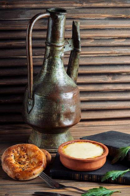 Ein traditionelles tandirbrötchen mit einem topf joghurt. Kostenlose Fotos
