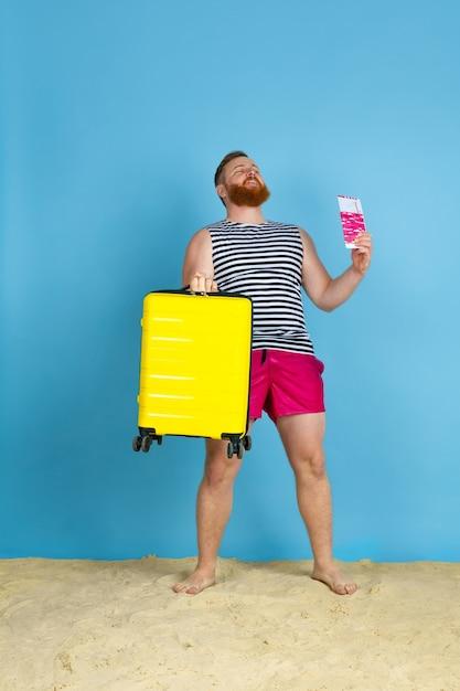 Ein traum wird wahr. glücklicher junger mann mit tasche, die für das reisen auf blauem studiohintergrund vorbereitet wird. konzept der menschlichen gefühle, gesichtsausdruck, sommerferien, wochenende. sommerzeit, meer, meer, alkohol. Kostenlose Fotos