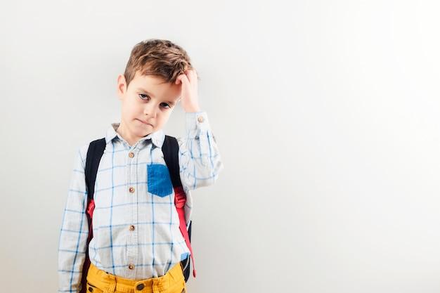 Ein trauriger junge mit einem rucksack gegen einen weißen hintergrund. Premium Fotos