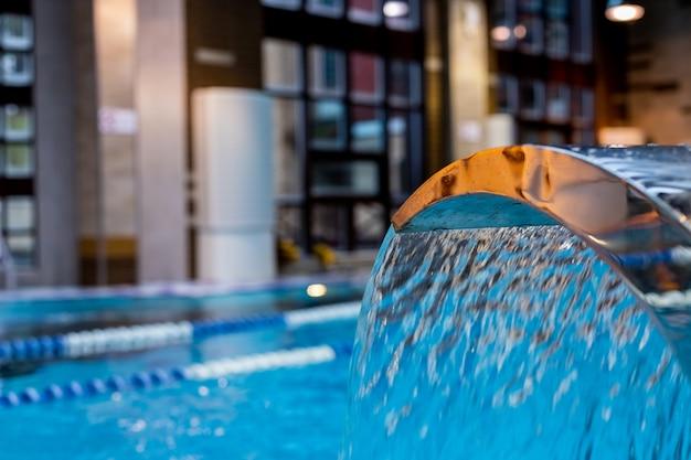 Ein türkisfarbener wasserfall, rücken- und schultermassage im pool. Premium Fotos