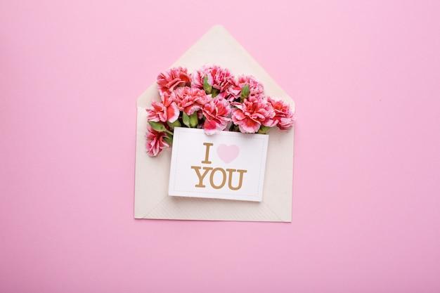 Ein umschlag mit rosa blumen und einer karte ich liebe dich auf rosa Premium Fotos