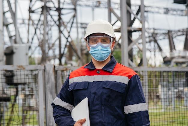 Ein umspannwerkingenieur inspiziert moderne hochspannungsgeräte in einer maske zum zeitpunkt der pondämie. energie. industrie. Premium Fotos